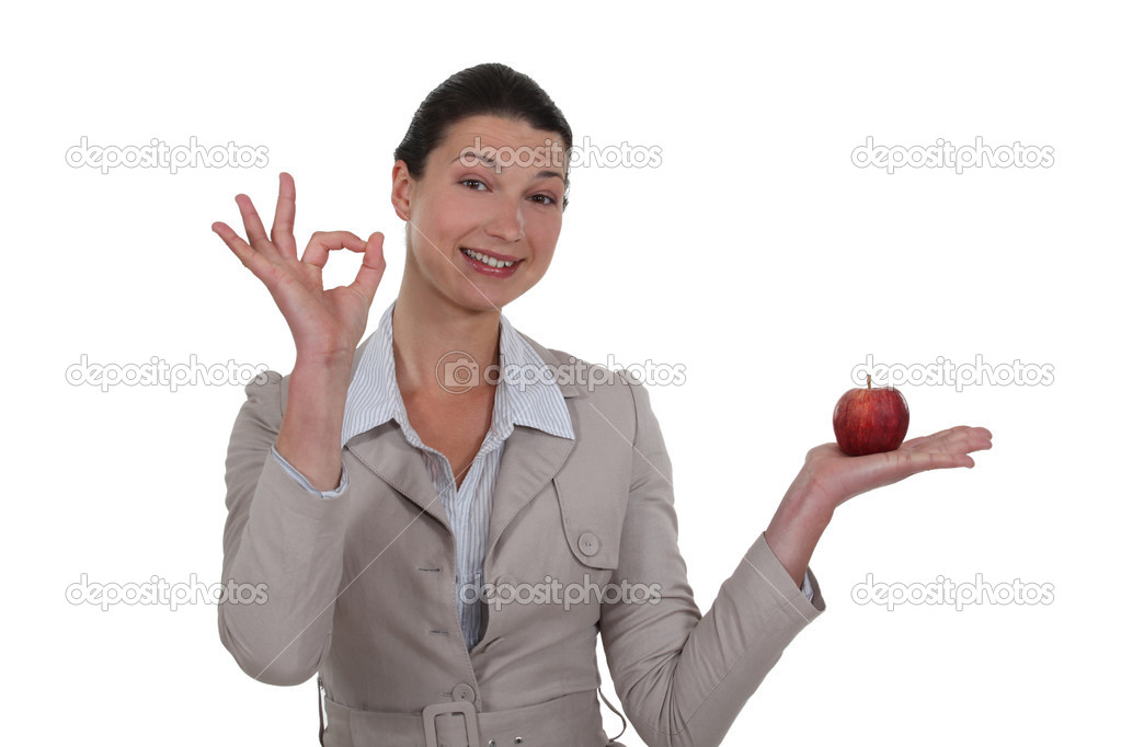 Woman holding an apple and giving the OK sign — Stock Photo #9805363