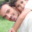 Father giving son piggy back outdoors — Stock Photo