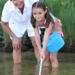 Little girl fishing in pond with mother — Stock Photo