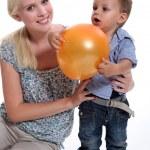 en mamma och hennes lilla son leker med en ballong — Stockfoto