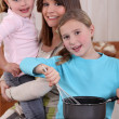 Mother and two young daughters cooking - Stock Photo