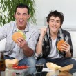 Father and son eating burgers in front of TV — Stock Photo #9811396