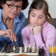 Young girl playing chess with grandma - Foto Stock