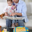Father and daughter at home reading a book — 图库照片
