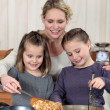 Stock Photo: Mother and daughters cooking pancakes