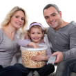 Family with a huge tub of popcorn — Stock Photo