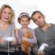 Daughter watching her parents play a video game — Stock Photo
