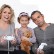 Daughter watching her parents play a video game - Stock Photo