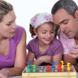 A family playing a board game together - Stock Photo