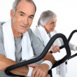 Stock Photo: Senior couple doing cardio machine
