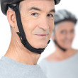 Old man and his partner wearing bike helmets — Stock Photo #9815884