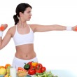 Woman with dumbbells in front of table full of fruit — Stock Photo