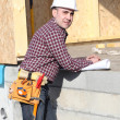Foreman overseeing construction of wooden house — Stock Photo #9816416