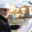 Architect stood with unfinished house in the distance - Stock Photo