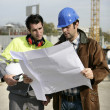 Construction site supervisors looking at a blueprint — Stock Photo
