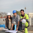 Three construction workers sharing their ideas — Stock Photo
