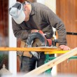 Man using circular saw on construction site - Stock Photo