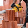 Builder cutting bricks to size — Stock Photo