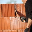 Mason cementing between bricks - Stock Photo