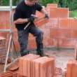 Stock Photo: Mason hitting bricks to make slight adjustments