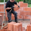 Mason hitting bricks to make slight adjustments - Stock Photo