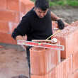 Stock Photo: Bricklayer erecting red brick wall