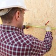 Man using tape measure to mark wooden panel — Stock Photo