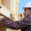 Worker nailing wooden framed house - Stock Photo