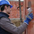 Stock Photo: Bricklayer checking brick wall