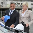 Male and female architects stood by car - Foto Stock