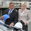 Male and female architects stood by car - Stock Photo