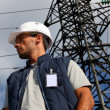 Worker standing in front of an electricity pylon — Photo