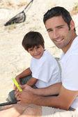 Vater und sohn sitzen auf dem boden — Stockfoto
