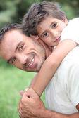 Vader geven zoon piggy terug buitenshuis — Stockfoto