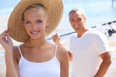 Pretty blonde with sun hat and boyfriend in background — Stock Photo