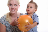 Mother and son holding a balloon. — Stock Photo
