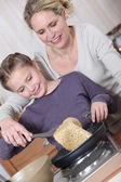 Mother and daughter cooking pancakes — Stock Photo