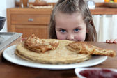 Greedy girl looking at pancakes — Stock Photo