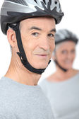 Old man and his partner wearing bike helmets — Stock Photo