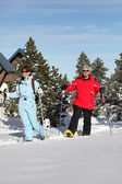 Mature couple walking in snow shoes — Stock Photo