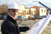 Architect stood with unfinished house in the distance — Stock Photo