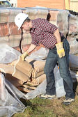 Tradesman lifting shingles — Stock Photo