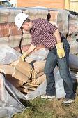 Tradesman lifting shingles — Stock Photo