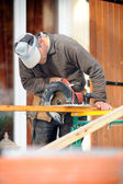 Man using circular saw on construction site — Stock Photo