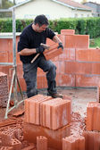 Mason hitting bricks to make slight adjustments — Stock Photo