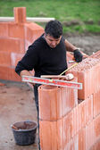 Bricklayer erecting red brick wall — Stock Photo