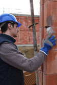Bricklayer checking brick wall — Stock Photo