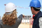 Tradesman and an engineer working together on a construction site — Stock Photo