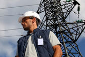Worker standing in front of an electricity pylon — Stockfoto