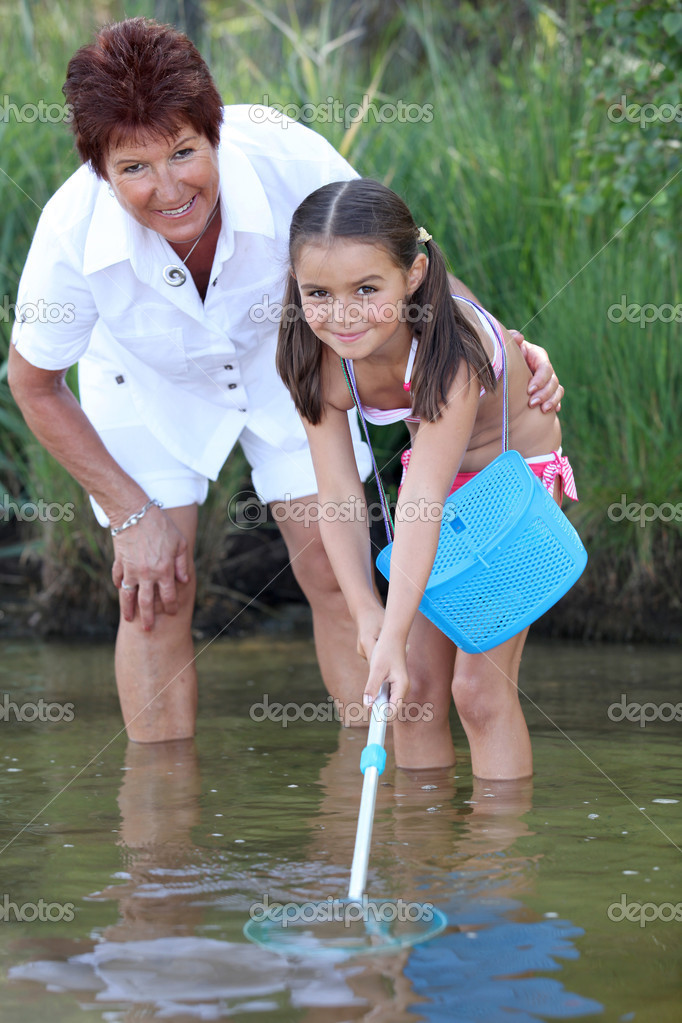 Little girl fishing in pond with mother stock photo for Little girl fishing pole